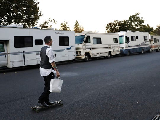 In this photo taken Oct. 5, 2017, a man skates past a row of RVs where people live and sleep in the heart of silicon valley in Mountain View, Calif. Apartments across the street start at over $3,000 a month. The booming economy along the West Coast has led to an historic shortage of affordable housing and has upended the stereotypical view of people out on the streets. Reporting by The Associated Press finds that many of them are employed, working as retail clerks, plumbers, janitors _ even teachers. They go to work, sleep where they can and buy gym memberships for a place to shower. (AP Photo/Marcio Jose Sanchez)