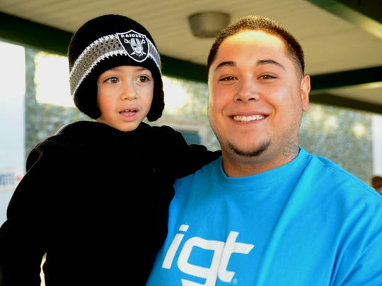 Derek Butler, 25, holds his son as he walks out of the polling site at Hug High School on Tuesday.