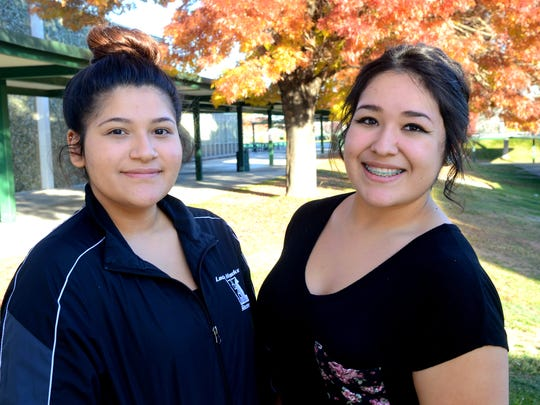 Ofelia Macias, 20, left, and Kimberly Chavez, 18, right, stand outside the polling site at Hug High School on Tuesday.