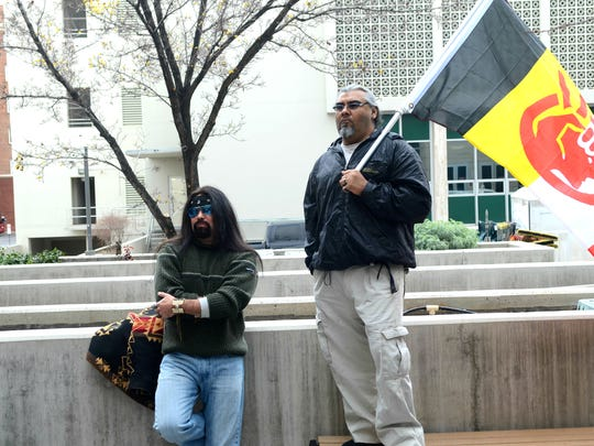 Two participants stand and watch as people gathered for a prayer circle Tuesday outside the Reno Justice Court.