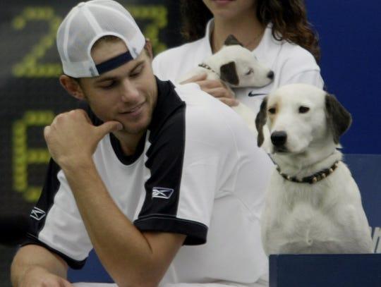 Andy Roddick checks out RCA mascot Nipper after winning