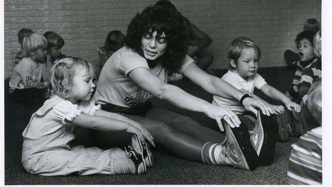 Jessica Hawkins (left) and Alicia Young (right) mimic instructor Reva Hall's stretches at Happy Days Daycare in Nixa in 1984.