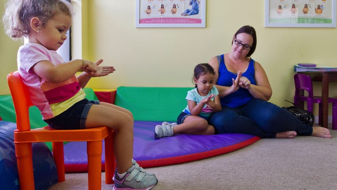 Lola Soto, 3, learns sign language at Two Happy Hands. Her sister Lilyana, 4, and mother Caryn Davis-Soto are in the background.