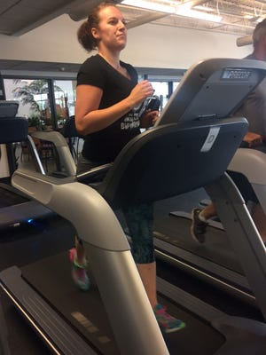 Julia Flanagan of Howard runs on a treadmill at the Bellin Fitness Center in Ashwaubenon. The 27-year-old has lost more than 75 pounds after being diagnosed with a hormonal disorder last year. She plans to run the Bellin Women's Half Marathon in Green Bay for the first time Saturday morning.