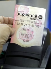 A store clerk pulls a Powerball ticket after being printed for a customer at a local grocery store in Hialeah, Florida on February 4, 2015.