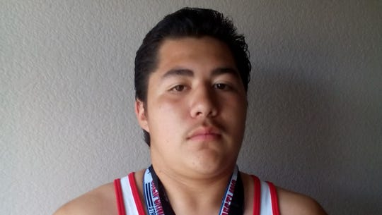 Zachary Ruelas poses with some of his medals he's earned