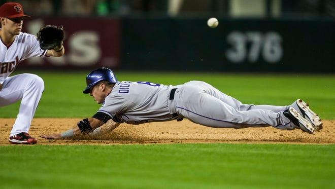 Diamondbacks infielder Chris Owings (16) attempts to get Rockies outfielder Corey Dickerson (6) out at second base during the Arizona Diamondbacks and Colorado Rockies baseball game at Chase Field on Monday, April 28, 2014 in Phoenix, Arizona.