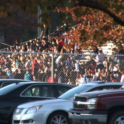 Newark High School students wait in the football stadium stands as police search the school after a bomb threat was called in Friday.