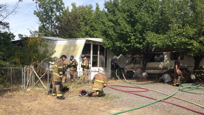Firefighters on Wednesday clean up a modular home after a blaze destroyed the building in eastern Farmington.