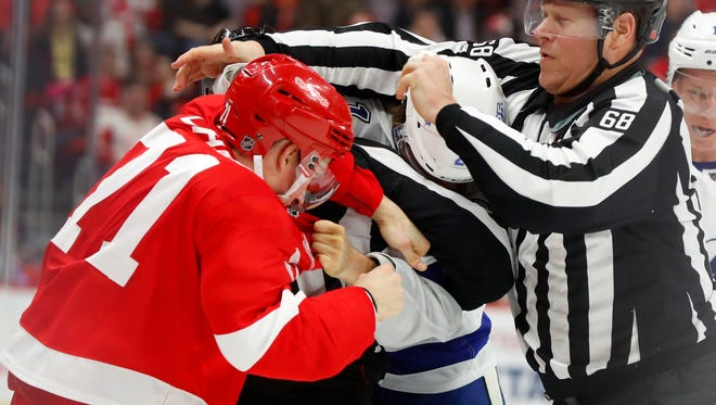 Linesman Scott Driscoll (68) tries to break up a fight between Red Wings center Dylan Larkin (71) and Lightning center Brayden Point (21) in the first period on Sunday, Jan. 7, 2018, at Little Caesars Arena.