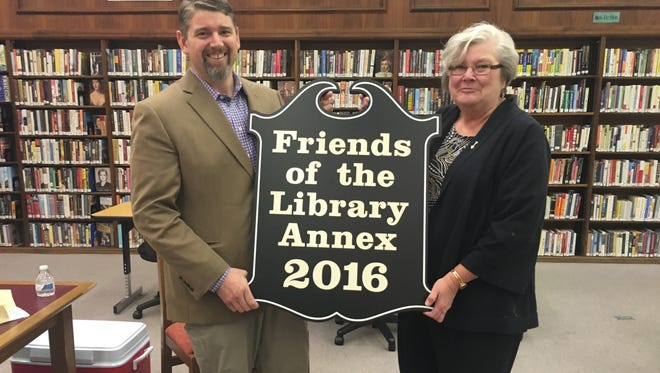 Colby Fry, president of the board of trustees of Shippensburg Public Library, presents a sign to Paula Yasenchak, president of the Friends of the Shippensburg Public Library, renaming the library annex in honor of the volunteers who run the Book Nook used book store.