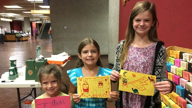 Mae, 5, Ava, 9, and Lily Hooten, 11, display some of the 40 hand-drawn messages of thanks distributed Thursday to law enforcement officers at the City County Building.