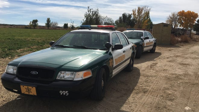 A pair of San Juan County Sheriff's Office cars are parked on Friday at a home on County Road 4990 east of Bloomfield as police searched for a plane that crashed near the San Juan River.
