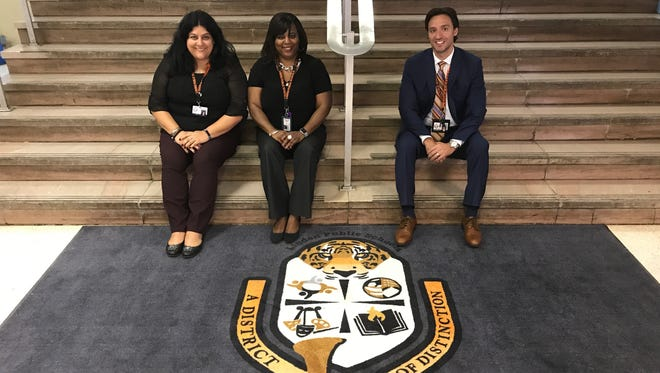Soehl Middle School Vice Principal Isabella Scocozza, left, Vice Principal Gwendolyn Long and Principal Richard Molinaro sitting by one of the main lobby's new welcome mats with the school name and Linden Public Schools logo.