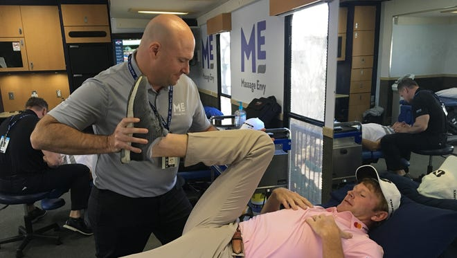 Massage Envy physical therapist Corey Hug stretches out PGA Tour golfer Brandt Snedeker after his practice round for the Waste Management Phoenix Open on Tuesday at TPC Scottsdale.