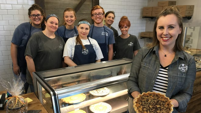 Workers at Buttermilk Sky Pie Shop in Murfreesboro stand behind the counter as general manager Miranda Smith holds the I-40 pie, which features pecan, chocolate chip and toasted coconut.