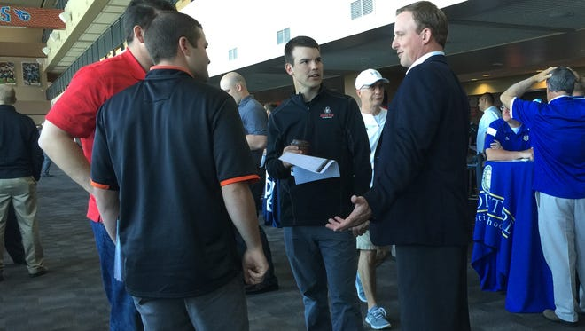 Austin Peay's Will Healy (middle) and Tennessee Tech's Marcus Satterfield (left), both in their first year as head coach at their respective programs,  talk with other coaches at the second annual Titans Recruiting Fair at Nissan Stadium Tuesday.