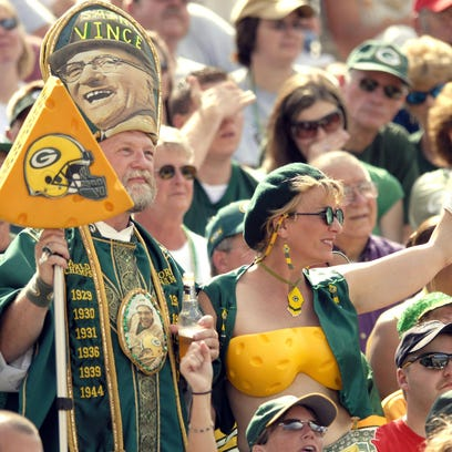Green Bay Packers fans cheer on their team while wearing