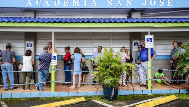 Puerto Rican citizens wait in line to vote during the fifth referendum in San Juan, Puerto Rico, Sunday, June 11, 2017. Puerto Ricans are getting the chance to tell U.S. Congress on Sunday which political status they believe best benefits the U.S. territory as it remains mired in a deep economic crisis that has triggered an exodus of islanders to the U.S mainland. Congress ultimately has to approve the outcome of Sunday's referendum that offers voters three choices: statehood, free association/independence or current territorial status. (AP Photo/Carlos Giusti)