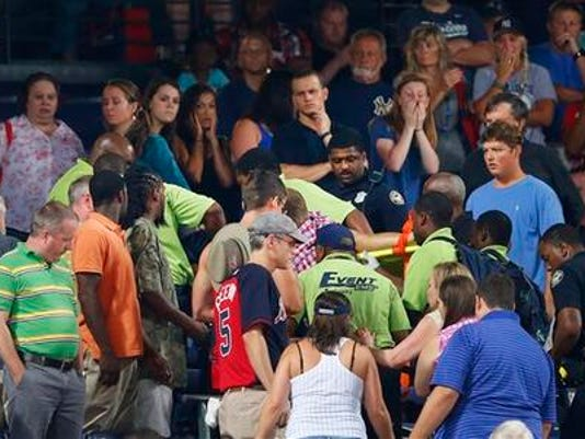 Rescue workers carry an injured fan from the stands at Turner Field during a baseball game between Atlanta Braves and New York Yankees, Saturday, Aug. 29, 2015, in Atlanta. The fan fell from the upper deck into the lower-level stands and was given emergency medical treatment before being taken to a hospital. (AP Photo/John Bazemore)