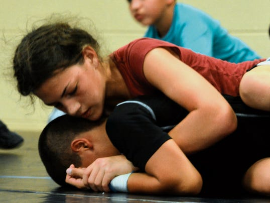 Kaitlynne Bindel, 12, takes control while wrestling against Anthony Fuentes, 11, Friday at the first Team Georgie Wrestling Camp at Black River Village Convention Center in South Carlsbad.