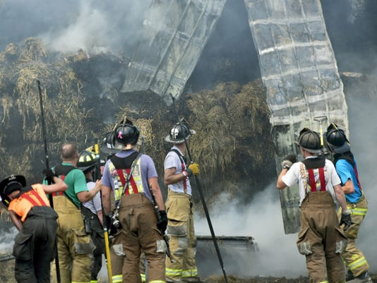 Part of a barn falls during a fire Sunday on Warm Spring Road. Two barns located about 500 yards down a dirt lane off Pa. 995 were destroyed.