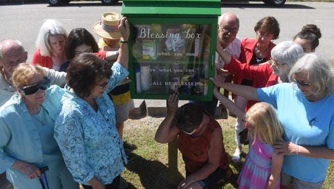 Attendees at a ceremony to dedicate Cotter's new blessing box lay their hands on it while pastor Jimmie Snow leads the group in a prayer Tuesday. The box offers food, toiletries and household items to those in need.