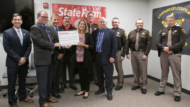 From left, Thom Connolly, State Farm grass roots specialist, Blaine Koops, CEO/executive director of the Michigan Sheriffs' Association, Dan Eskola,  Brandon Krugh and Trinesha Goebel of State Farm, Livingston County Sheriff Mike Murphy, Geof Geline of State Farm, Mason County Sheriff Kim Cole, Mason County Chief Dep. Derrek Wilson  and Livingston County Undersheriff Jeffrey Warder assemble Thursday, April 12, 2018 as State Farm Insurance presents the Michigan Sheriffs' Association with a check for $25,896 for the association's program entitled Sheriffs Telling Our Parents & Promoting Educated Drivers, or S.T.O.P.P.E.D.