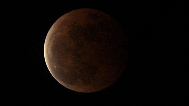 An orange moon is seen in the sky during a total lunar eclipse in Quezon City, suburban Manila on October 8, 2014.