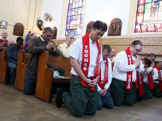 Inmates pray during a Mass with Cardinal Timothy Dolan,