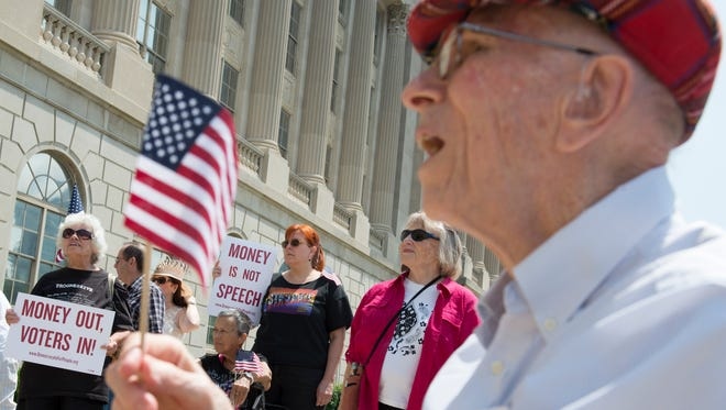Tom Moffett, 90, holds an American flag during a rally to limit campaign financing in front of the federal courthouse. July 2, 2014