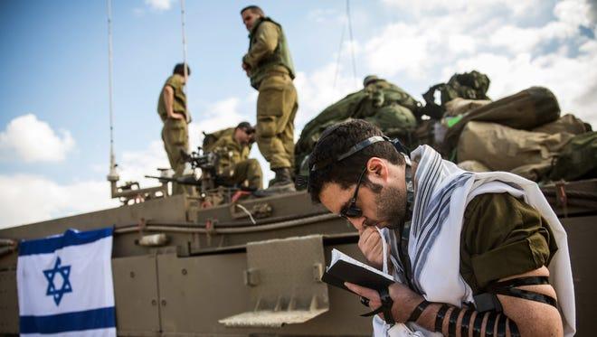 An Israeli reservist prays near the Israeli-Gaza border.