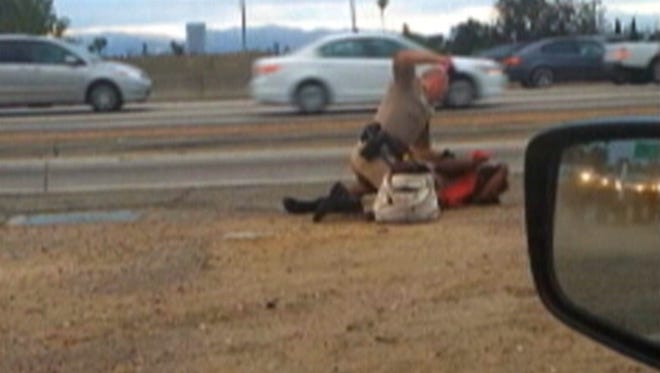 In this July 1, 2014 file image made from video provided by motorist David Diaz, a California Highway Patrol officer straddles a woman while punching her on the shoulder of a Los Angeles freeway.