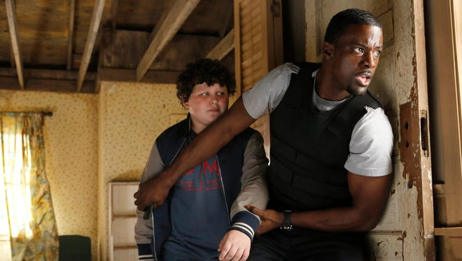 A rookie Secret Service agent (Lance Gross) protects one of the students who got away (Joshua Erenberg) in NBC's 'Crisis.'