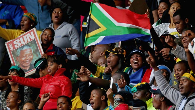 Some of the first people to arrive at the 95,000-seat FNB Stadium sing and dance before the start of the official memorial service for former South African president Nelson Mandela on Dec. 10.