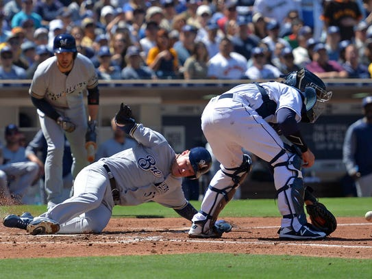 Brewers pitcher Chase Anderson begins his slide.