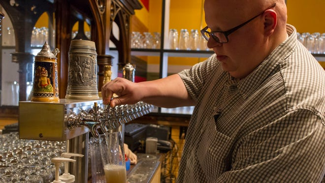Territorial Brewing Company Co-owner, Tim Davis, pours a glass of their Engleharn, a North German Pils style beer.