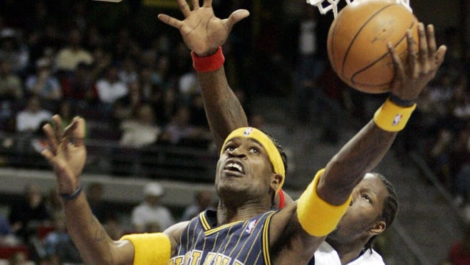 Indiana Pacers forward Stephen Jackson (1) makes a layup while defended by Detroit Pistons center Ben Wallace (3) during the first quarter at the Palace in Auburn Hills, Mich., Friday, March 25, 2005.