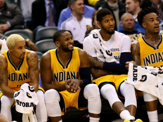 Indiana Pacers teammates C.J. Miles (0) and Paul George (13) sit on the bench as the time ticks off the clock in the win against the Toronto Raptors at Bankers Life Fieldhouse on Dec. 14, 2015.