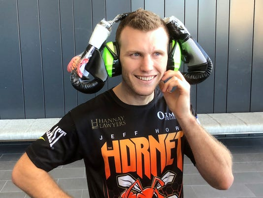 Boxer Jeff Horn wears a pair of boxing gloves on top of earmuffs Tuesday, Dec. 12, 2017, after his a weigh-in for his next fight in Brisbane, Australia. Horn will defend his WBO welterweight world title against Britain's Gary Corcoran on Wednesday. (AP Photo/John Pye)