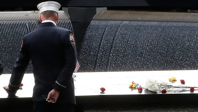 A firefighter touches the names of the firefighters who died in the attacks carved in the south pool during 15th anniversary ceremony of the attacks of the World Trade Center at the National September 11 Memorial, Sunday in New York.