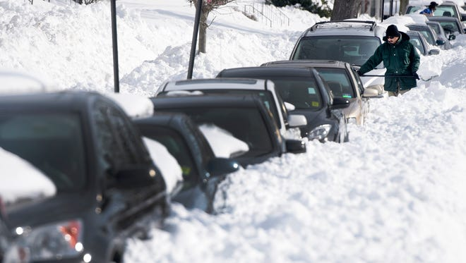 Ragi Puthur digs his car out from snow outside his home in Towson, Md., Monday, Jan. 25, 2016. East Coast residents continued to dig themselves out after a massive weekend snowstorm.