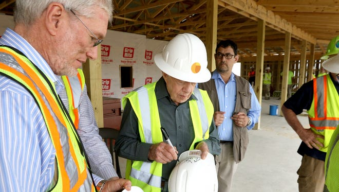 Former president Jimmy Carter signs a hard hat for Ken Ham, president, CEO, and founder of Answers in Genesis after Carter toured the Ark Encounter under construction in Williamstown.