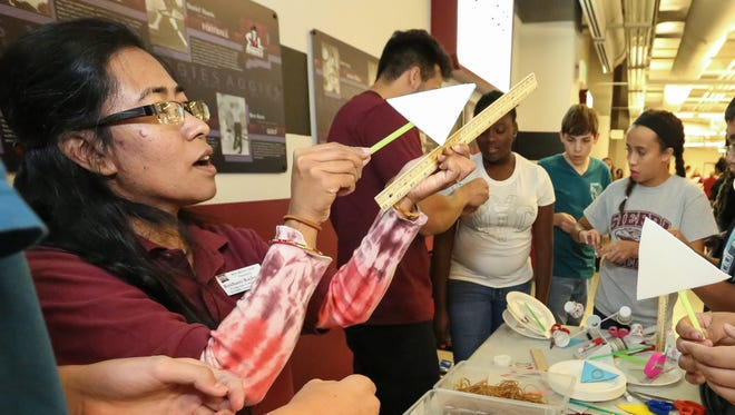 Roshani Rajbanshi, Stem Outreach Center program coordinator, shows local eighth graders how to make paper plate airplanes on Monday at the Pan American Center during an Unmanned Aircraft Systems Roadshow (drones) hosted by New Mexico State University.