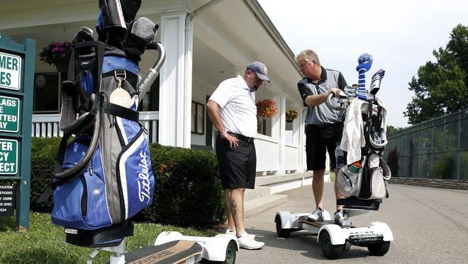Enquirer Sports Strategist Jason Hoffman, left, gets a lesson about the GolfBoard from PGA golf professional Harry Alexander at Clovernook Country Club last year. Alexander was recently named the club's general manager.