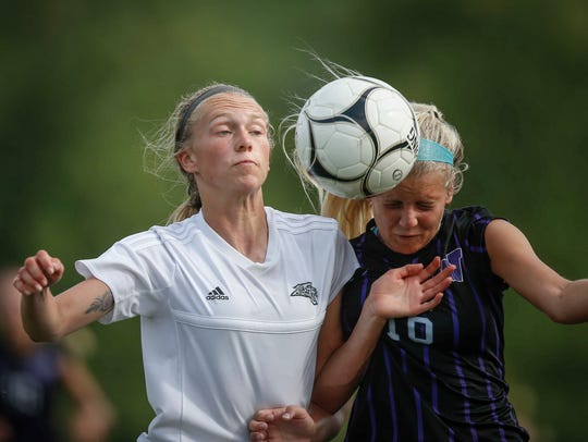 Ankeny Centennial junior Olivia Wee, left, battles