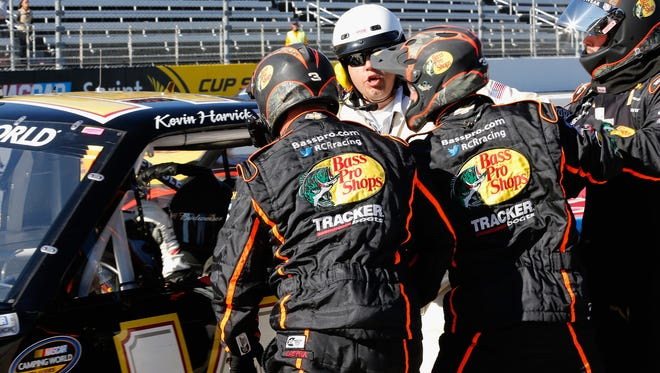 Crew members for Ty Dillon (not pictured) are restrained by an official while surrounding Kevin Harvick's truck on pit road at Martinsville Speedway.
