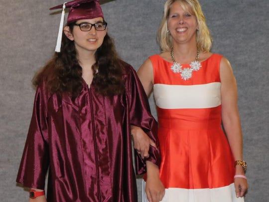 Joslyn Sessel takes the graduates' walk, escorted by