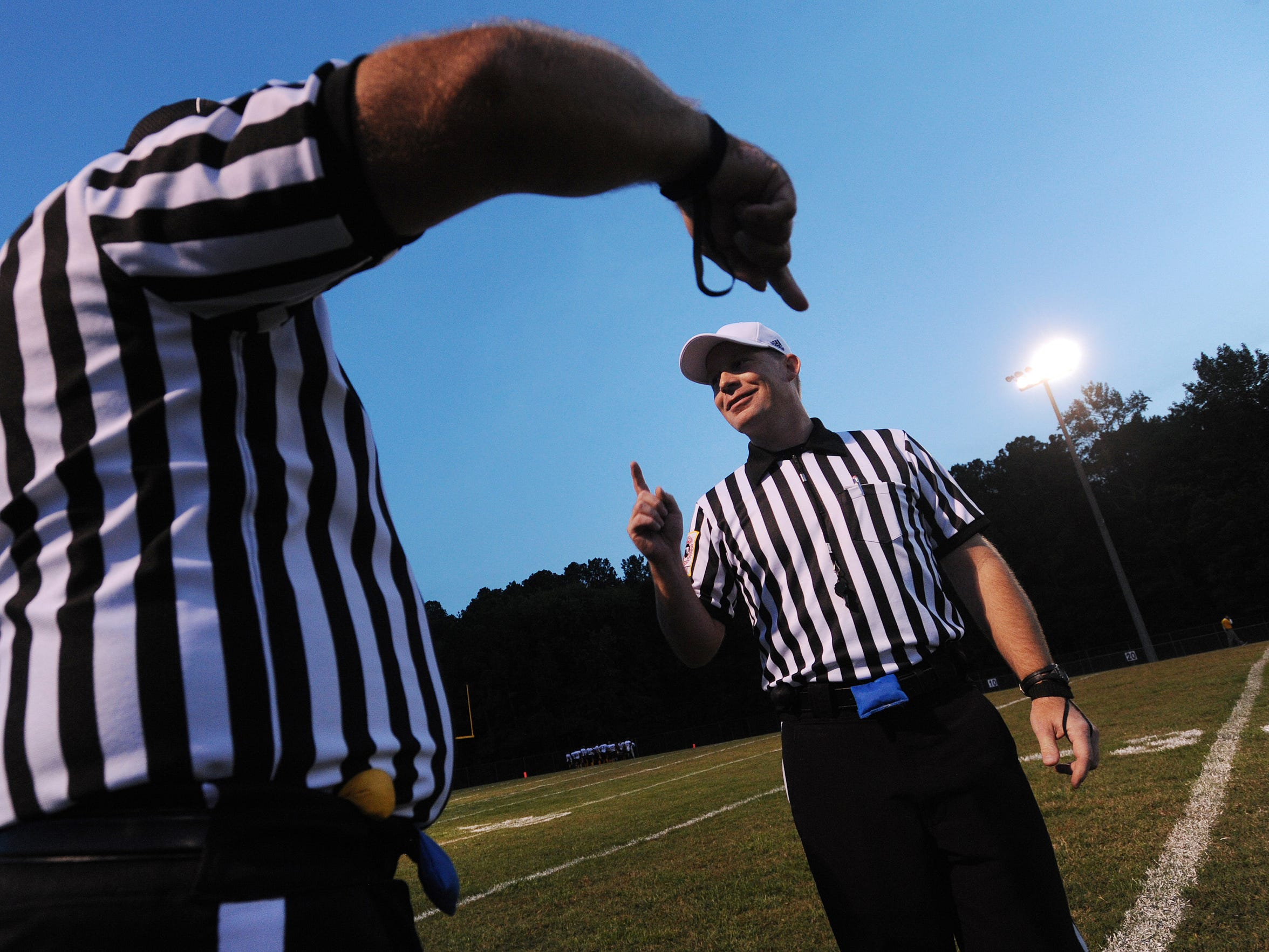 Referee Chuck Brosch, right, speaks with one of his crew members before the start of the Nandua and Washington football game on Friday, Oct. 3, 2014 in Onley, Va. Brosch has been a football official for 21 years and is a member of the Bayside Football Officials Association.