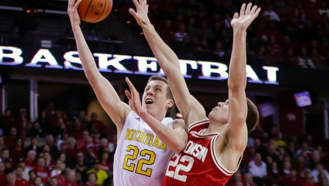 Michigan's Duncan Robinson, left, shoots against Wisconsin's Ethan Happ during the first half of an NCAA college basketball game, Sunday, Feb. 28, 2016, in Madison, Wis.